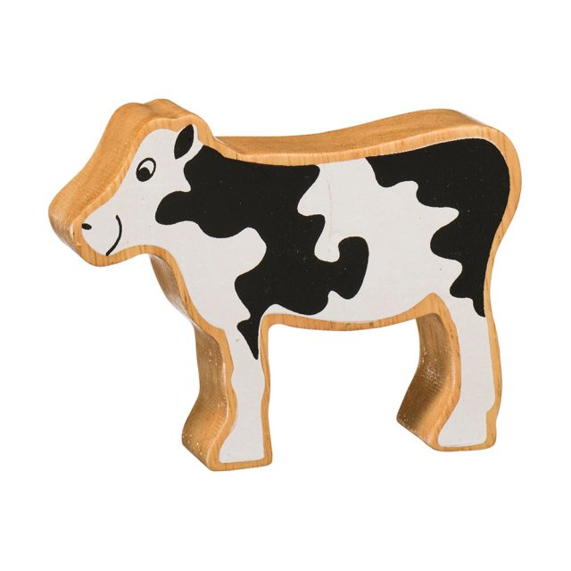 A chunky wooden black and white calf toy figure in profile with a natural wood edge