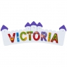 Large, flat wooden name plaque in white and purple castle design with Victoria spelt in multicoloure