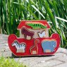 Wooden red Noah's ark shape sorter tray with six removable animals against grass backdrop.