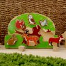 Wooden green tree shape sorter tray with six removable colourful animals with wicker backdrop.