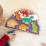 Child playing with purple volcano shape sorter toy with removable dinosaur figures