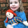 Child holding mum rag doll with red hair and a checkered multicoloured dress