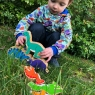 A child playing with a wooden turquoise diplodocus dinosaur toy figure, stacking them in the garden