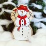 A chunky wooden white snowman toy figure in profile with a natural wood edge