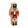 A chunky wooden red and white nutcracker toy figure in profile with a natural wood edge