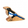 A chunky wooden magpie toy figure in profile with a natural wood edge